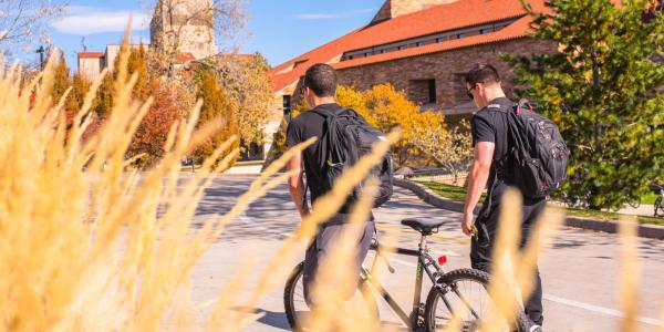 Students walk with bikes on campus