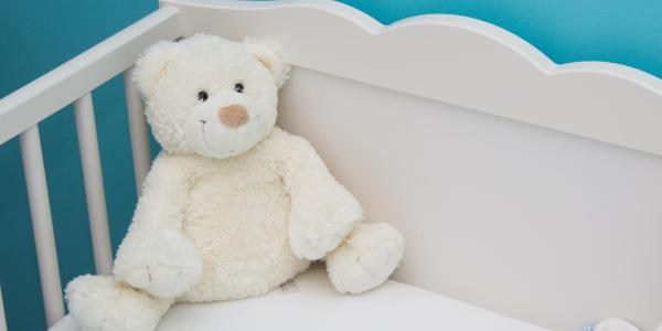 A baby crib with a stuffed white bear inside