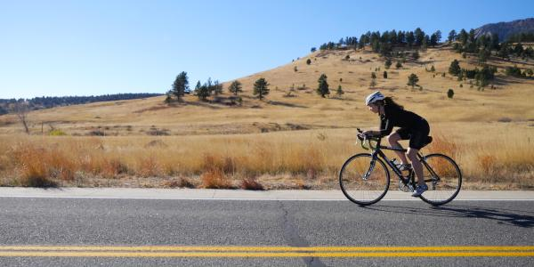 Woman bikes along highway, rolling hills