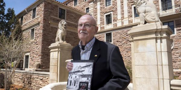 Campus Architect Emeritus Bill Deno poses for photo with new Body & Soul book