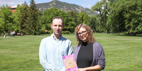 Walker Sampson and Heather Bowden hold their book on the CU Boulder campus