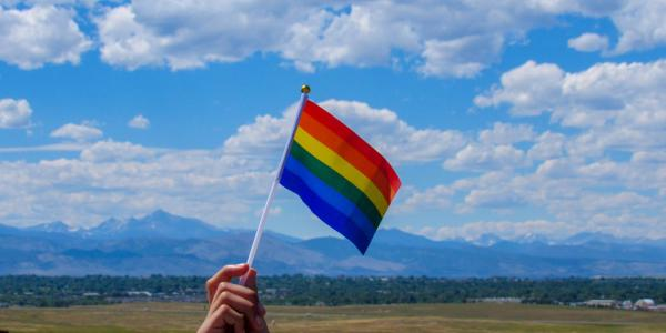 A pride flag in front of the Rocky Mountans