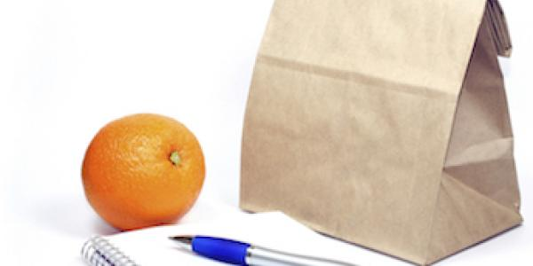 A brown paper bag, pen, and orange