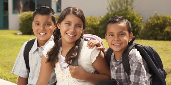 Two brothers and sister ready for school with backpacks on | Photo credit BUENO Center