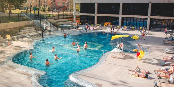Students playing volleyball and swimming in the Buff pool on campus