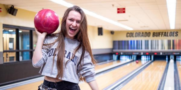 A student poses with a bowling ball at The Connection on campus