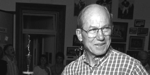 A black and white photo of Justice Byron White in a casual button down shirt with some trophies behind him.