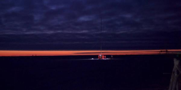 A panoramic image of the Arctic Sea ice and researchers at night