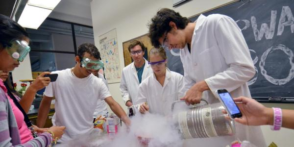 CU Boulder chemistry graduate student  leads experiments for high school students attending the Upward Bound program.