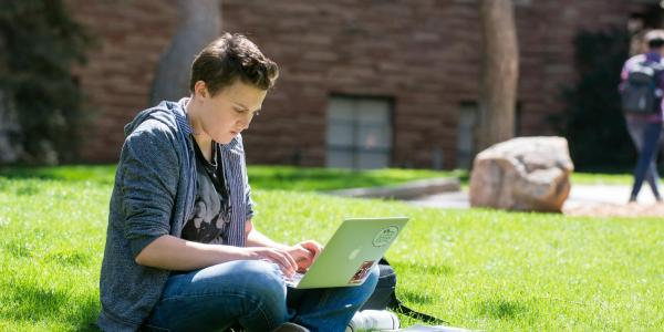 person working on laptop outside on campus