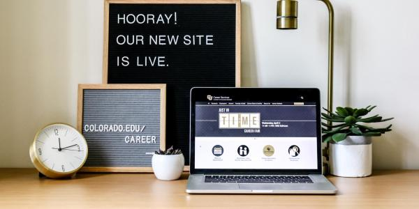 "Photo of laptop with new Career Services website, sign that says ""Hooray! Our new site is live."""