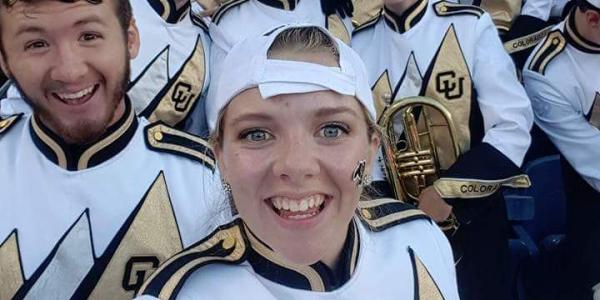 Marching band members in uniform and with their instruments pause for a selfie photo.