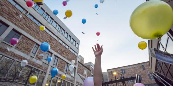 Students release biodegradable balloons into the air as part of a class project