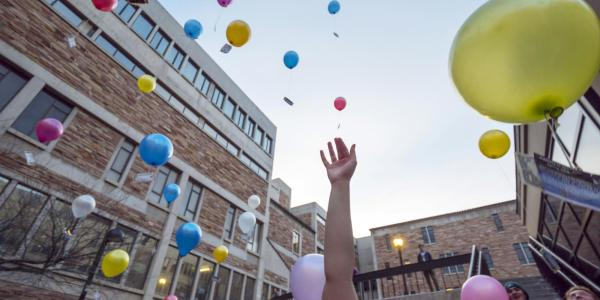 Students release biodegradable balloons as part of a class project