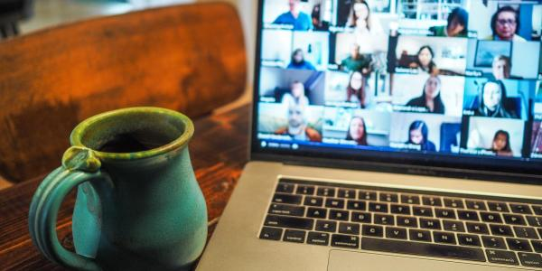 coffee mug next to a Zoom meeting on a laptop