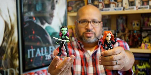 Christopher Bell poses with Gamora and Black Widow action figures