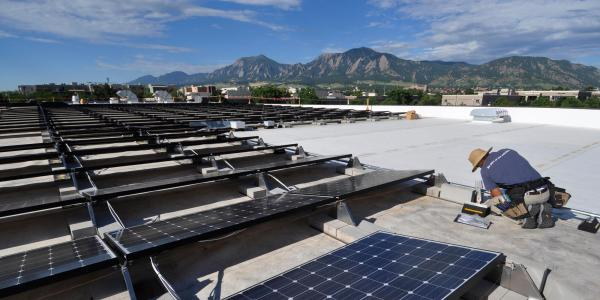 A technician installs solar panels on the roof of the building which houses the University of Colorado Center for Innovation and Creativity in Boulder.