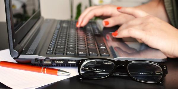 Person typing on computer, with pen and glasses nearby