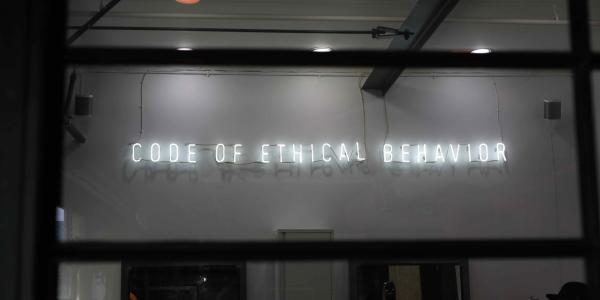 "A stock image of a neon sign that says ""Code of Ethical Behavior"""