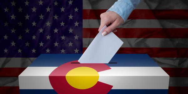 Person drops ballot in a drop box