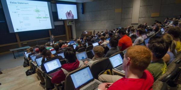 A large class of students is seated, looking at a screen in a lecture hall.