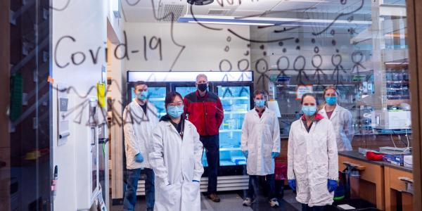 "Researchers pose in their lab behind glass with the words ""COVID Warriors"" written on it."