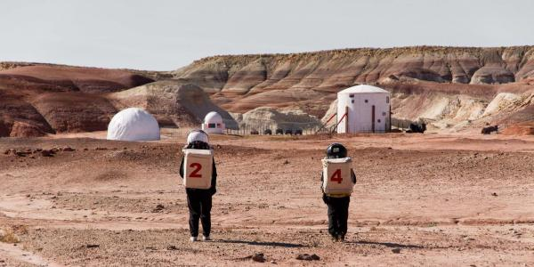 Two people wearing spacesuits walk through the Utah desert