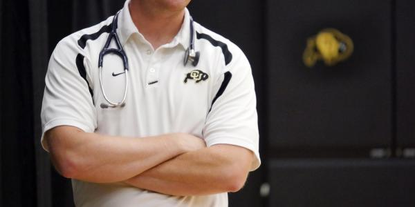 An unidentified man with arms crossed sports Buff gear and a stethoscope.