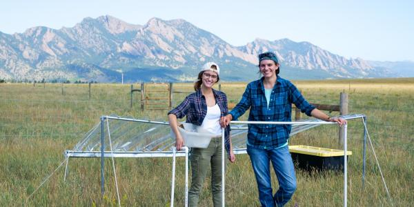 Graduate student Julie Larson and undergraduate Emily Koke in grass