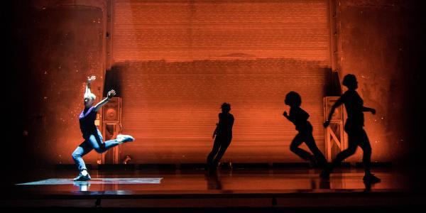 Dancers on stage in orange light