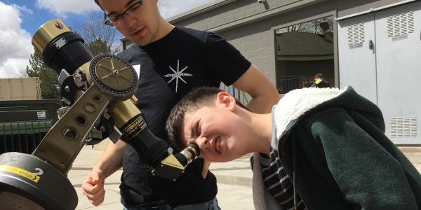 CU-STARs student volunteer helps child look through telescope