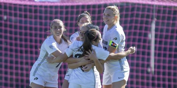 CU women's soccer team hug in celebration