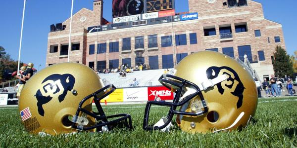 Two helmets are seen on the football field with the Dal Ward building in the background.