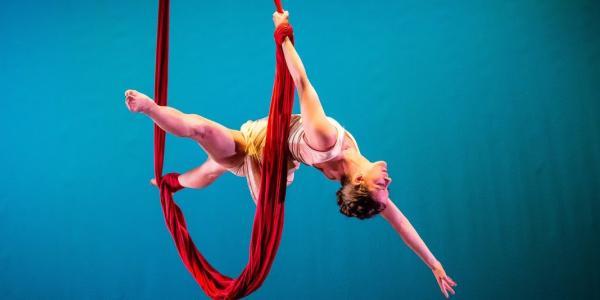 Danielle Garrison hanging a red fabric drape