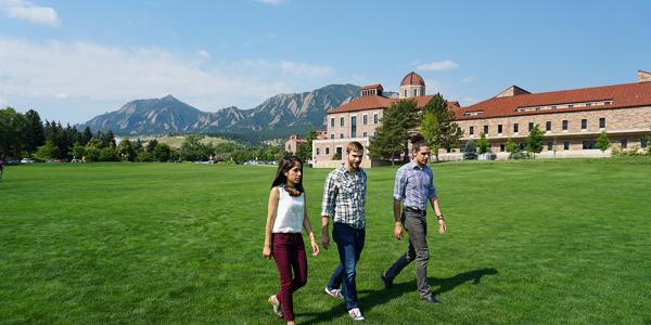 Students walking across Business Field toward the College of Engineering