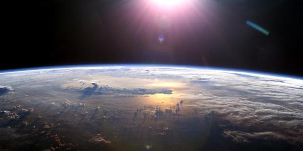 Sun rises above the Earth as seen from space.