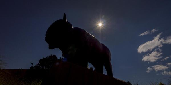 Ralphie statue silhouetted by an eclipsed sun