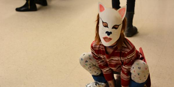 Young student dressed as feline superhero poses for photo