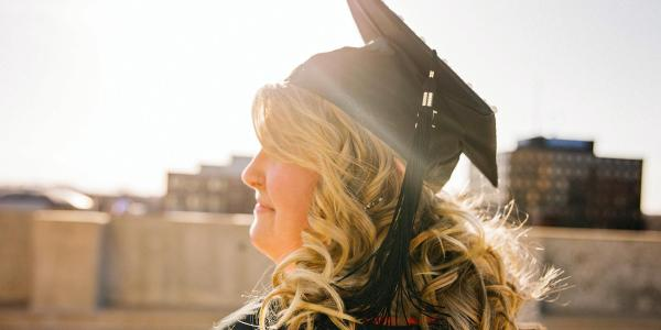 person in graduation cap and gown on rooftop alone