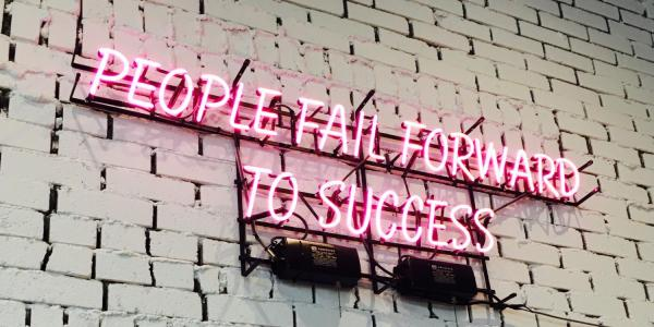 neon sign that says 'People fail forward to success'