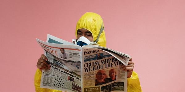 A stock image of a man in a hazardous materials suit reading a newspaper.