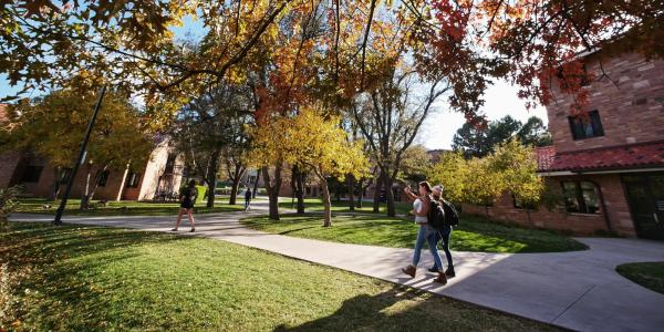 students walking on campus with fall foliage
