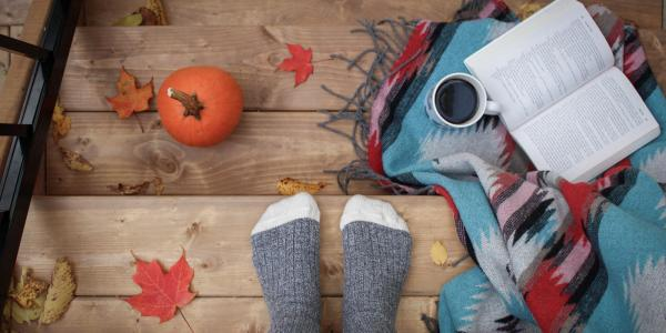 Stock image of someone sitting on steps with fall items around them
