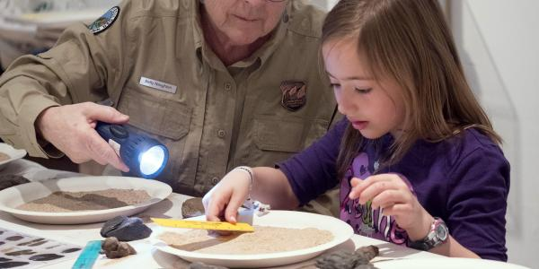 Preschooler examines dirt at a CU Museum of Natural History Family Day event