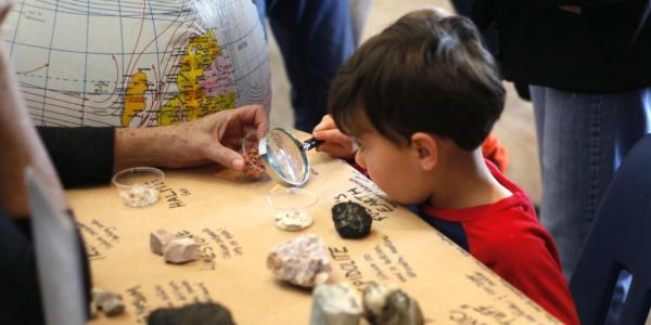 Kid looking at rocks through a magnifying glass