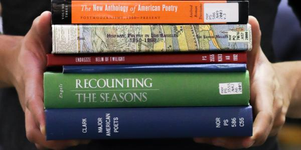 Campus community members holds stack of poetry books