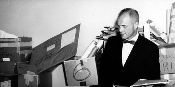 John Glenn looking through piles of mail