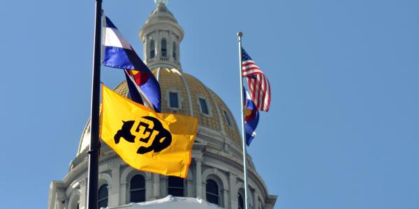 A CU, Colorado and United States flag at the Denver capitol building.