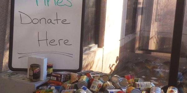 """Donate here"" Food for Fines sign sits next to donated food items"
