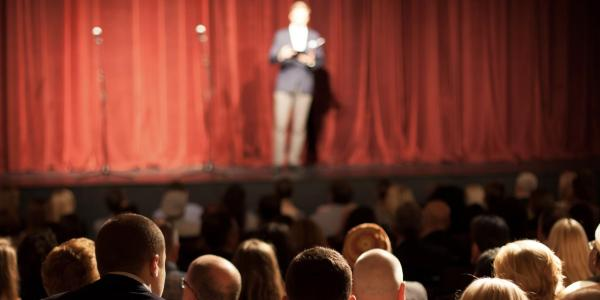 Stand up comedian on stage in front of an audience